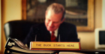 Baker at desk with desk plaque that reads, the Buck Starts Here