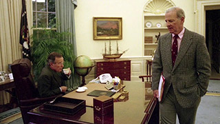 PPresident Bush seated at desk with Baker standing on other side of the desk.