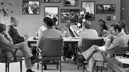 Gerald Ford at conference table with Jim Baker and seven others in a meeting room