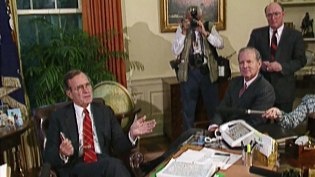 President Bush seated in chair with Baker and reporters gathered around.
