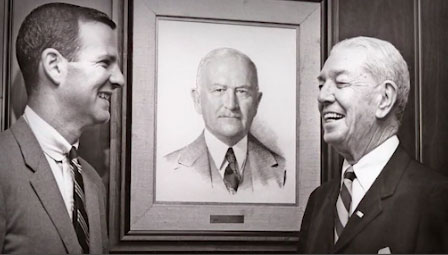 Jim Baker standing with his father in front of a portrait of his grandfather